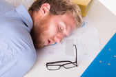 Worker sleeping on the desk in the office — Stock Photo