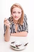 Woman eating insects with a fork — Stock Photo