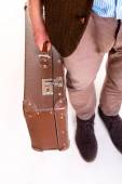 Legs of a man and suitcase in hand — Stock Photo