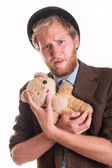Unhappy old-fashioned man hugs an old teddy bea — Stock Photo