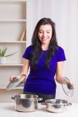 Girl  with cooking pans at kitchen — Stock Photo