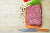 Fresh raw piece of meat lies on the kitchen blackboard — Stock Photo