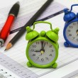 Miniature clocks showing 9 am and 5 pm on open agenda — Stock Photo #55786683