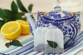 Tea bags, vintage teapot and fresh lemon — Stockfoto