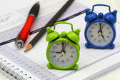 Miniature clocks showing 9 am and 5 pm on open agenda — Stockfoto