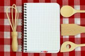 Notebook and wooden cooking utensils on red and white checkered tablecloth — Stock Photo