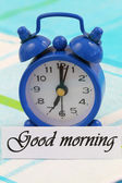 Good morning card with miniature clock showing 7 am — Stockfoto