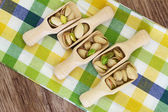 Pistachio nuts with and without shell on wooden scoops on checkered cloth — Stock Photo
