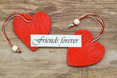 Friends forever card with two red wooden hearts — Stock Photo