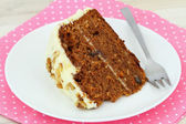 Carrot cake with walnuts and marzipan icing on pink napkin — Stock Photo