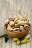 Pistachios with and without shell in wooden bowl with copy space — Stock Photo