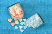 Colorful sugar hearts in transparent bottles on blue background — Stock Photo