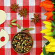 Spices, chilies and wooden spoons on checkered tablecloth — Stock Photo #65306125