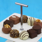 Selection of chocolates on white cake tray — Stock Photo #65307075