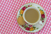 Tea in vintage porcelain cup on pink and white checkered cloth with copy space — Stock Photo