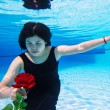 Asian woman under the water holding a rose — Stock Photo #56266945