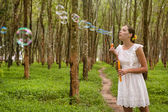 Woman blowing bubbles in forest — Stockfoto
