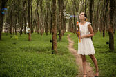 Woman blowing bubbles in forest — Stock Photo