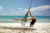 Woman on a swing on the beach — Stock Photo
