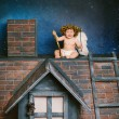 Baby angel sitting on the roof — Stock Photo #73934293
