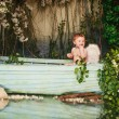 Baby with angel wings in a boat with flowers — Stock Photo #73934313