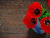 Red tulips on an antique wooden background — Stock Photo