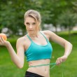 Sporty young woman with apple and measuring tape. Outdoors. — Stock Photo #57360181