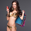 Pretty woman in gold bikini holding shopping bags and showing blank credit card — Foto Stock #59592395
