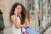 Beautiful young woman goes shopping — Stock Photo