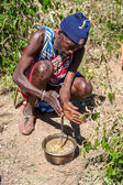 MASAI MARA,KENYA, AFRICA- FEB 12 Masai shaman is preparing a potion in traditional clothes, review of daily life of local people,near to Masai Mara National Park Reserve, Feb 12, 2010,Kenya — Stock Photo