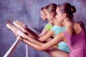Ballerinas stretching on the bar — Stock Photo