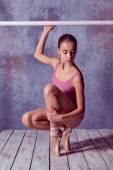 Ballerina stretching on the bar — Stock Photo