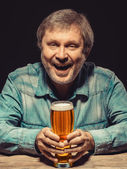 The smiling man in denim shirt with glass of beer — Stock Photo