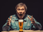 The screaming man in denim shirt with glass of beer — Stock Photo