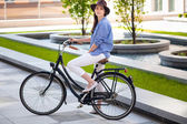 Pretty girl in hat riding a bicycle at street — Stock Photo