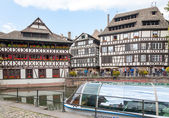 STRASBOURG, FRANCE - SEPTEMBER 26 2008: Strasbourg, water canal in Petite France area. timbered houses and trees in  Alsace, France. in the foreground water bus — Stock Photo