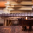Candle on wooden table with books in background — Stock Photo #62619069