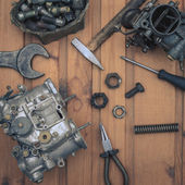 Carburetors for a car engine with tools on wooden table — Stock Photo
