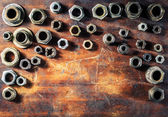 Screws on dirty wooden table — Stock Photo