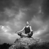 Woman doing yoga against the setting sun — Stock Photo