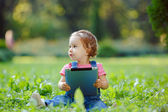 Child playing with tablet outdoors — Stock Photo