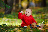 Cheerful baby in a red dress playing with yellow leaves — Стоковое фото