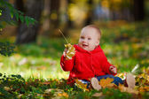 Cheerful baby in a red dress playing with yellow leaves — Stock Photo
