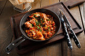 Fried meat in a frying pan tomato sauce — Stock Photo