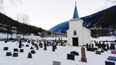 Church cemetery and wooden church covered snow — Stock Photo
