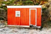 A small red cabin near rocks — Stock Photo