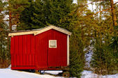 Red wooden house on the tool — Stock Photo