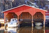 Red wooden garage for three boats — Stock Photo