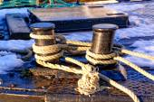 Gray ropes tied to cum on the fishing boat — Stock Photo