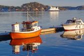 Small orange fishing boat with reflection in the water — Stock Photo